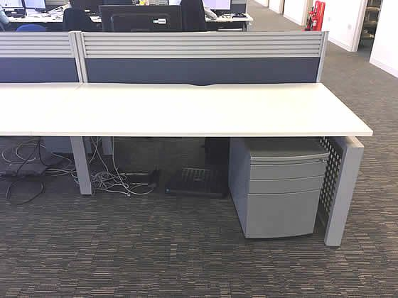 Further view of the white bench desks shown in the previous image.