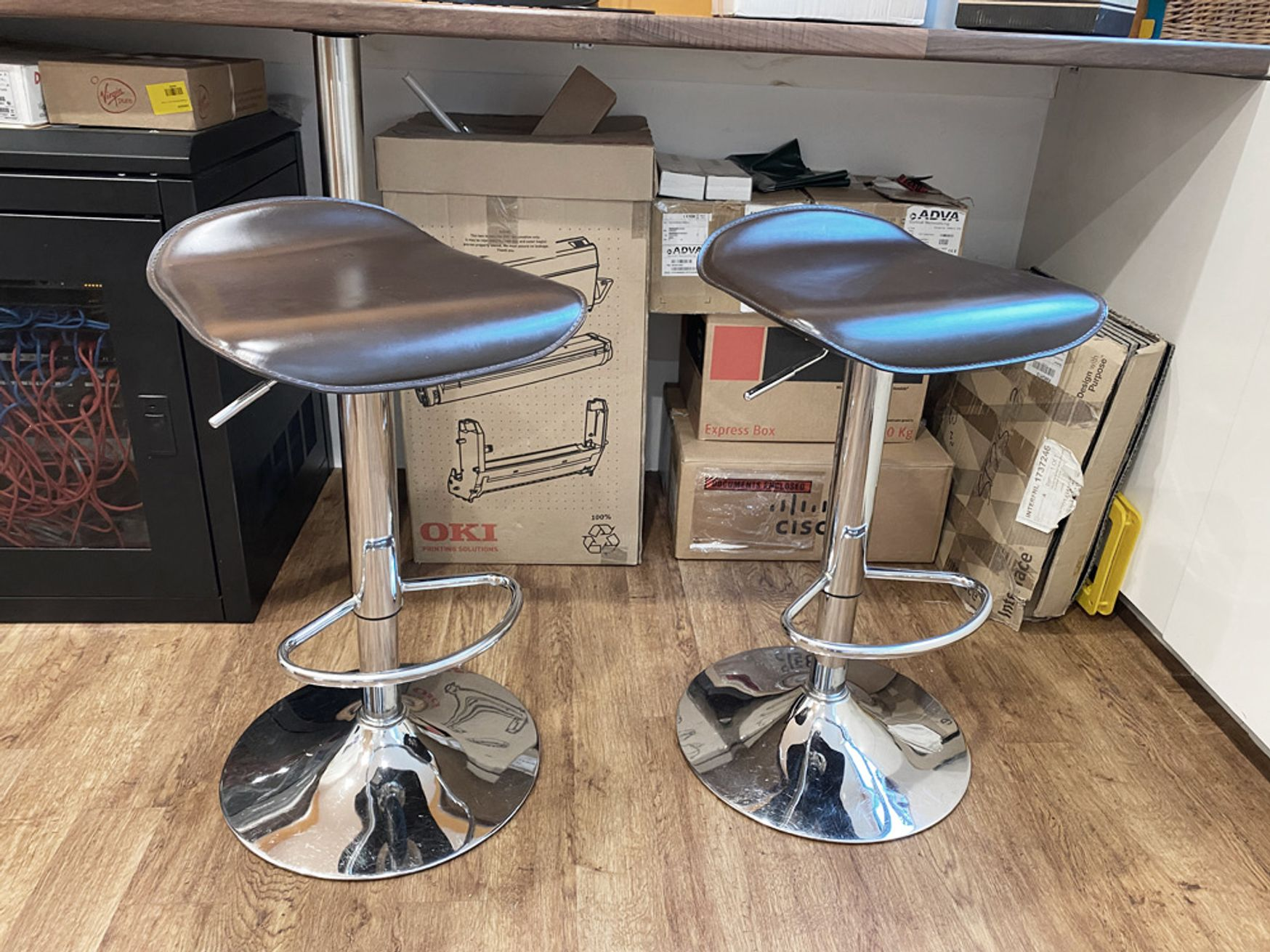 Stools with brown leather seats and chrome trumpet base