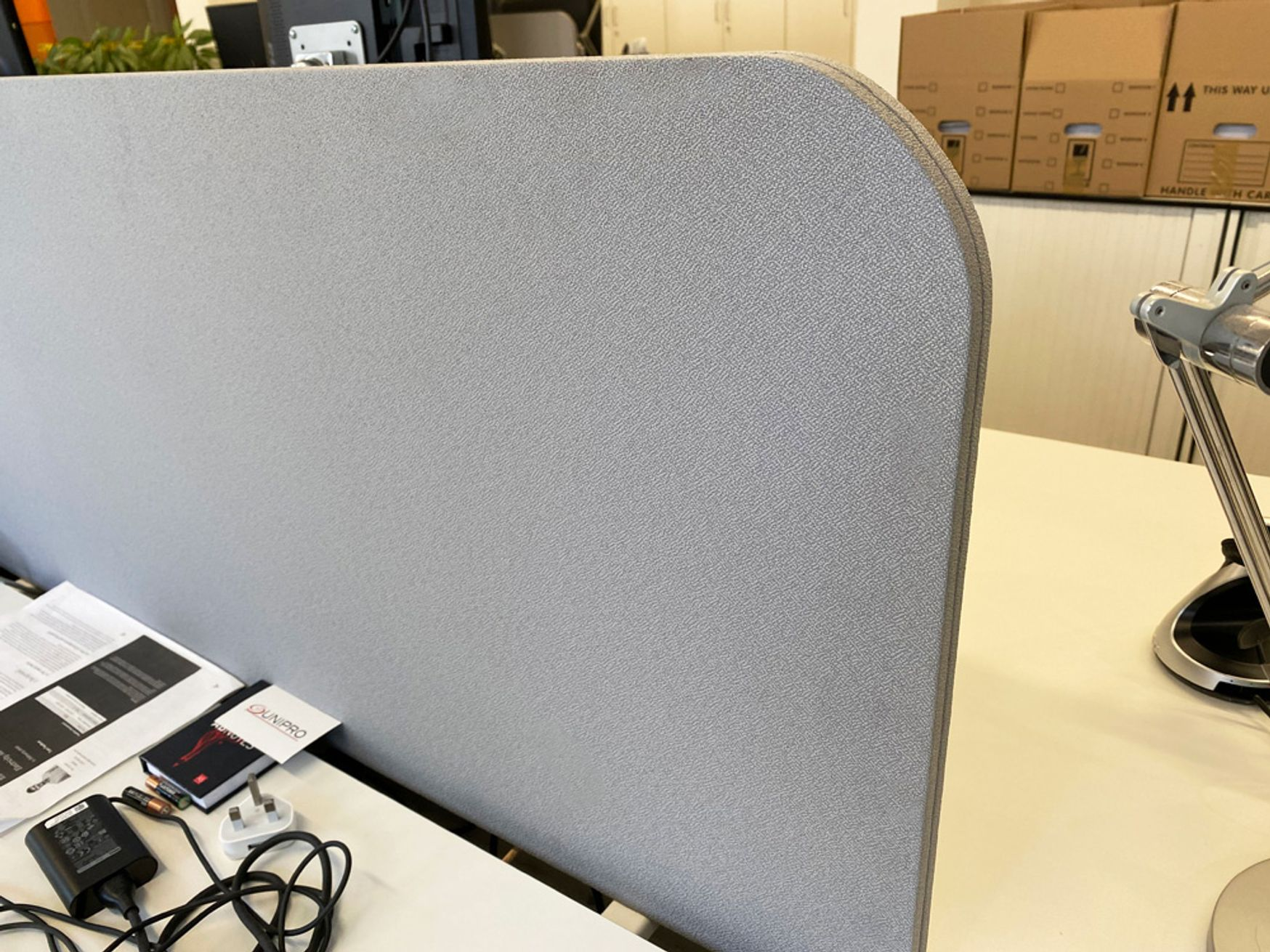 Desk dividing screens upholstered in grey fabric.