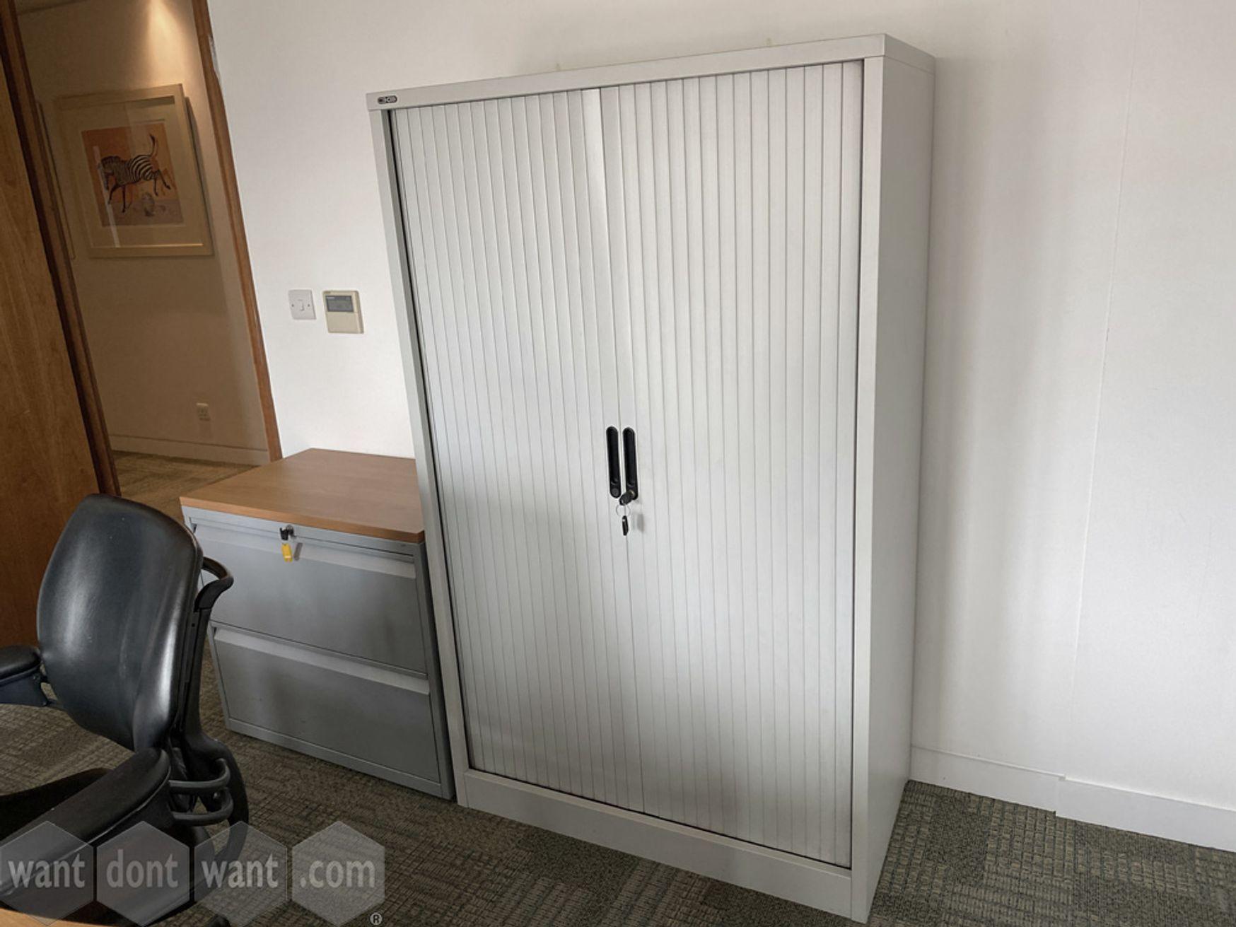 Used grey metal side tambour-door cupboard with shelves