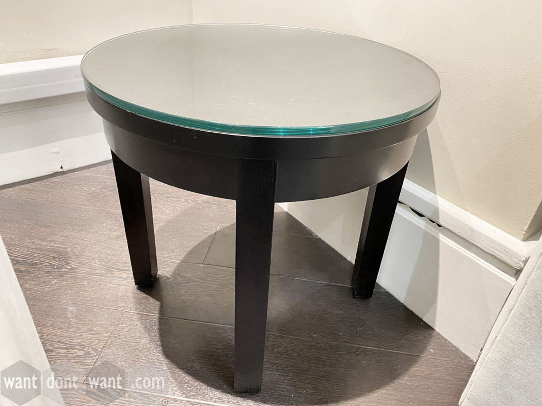 Used circular side table in dark mahogany finish with glass top