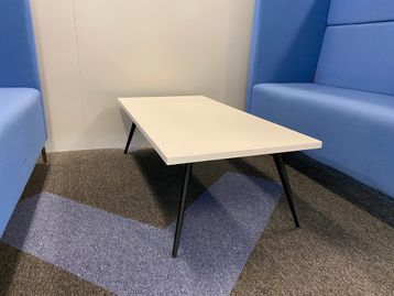 Used white coffee tables with splayed black legs.