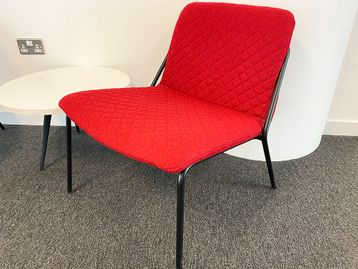 Used 'Sling' lounge chairs in red coloured quilted fabric with black metal legs.