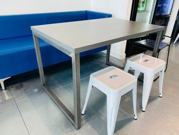 Urban style used cafe tables with grey tops and raw steel legs.
