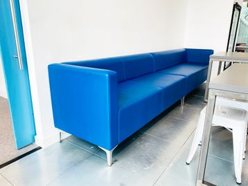 Large used blue leather banquet sofa