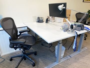 White used electric height adjustable desks in good condition.