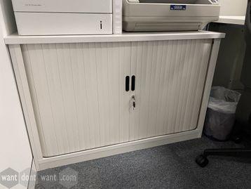Low side-tambour door storage cupboard with shelf.