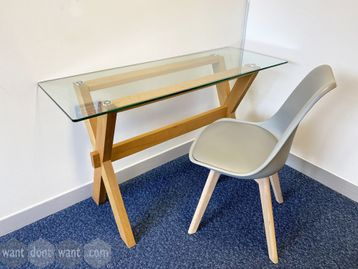 Used table with glass top supported by beech frame.