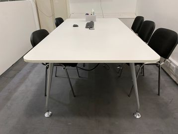 Used Mobili white meeting table with silver splayed legs and cable port