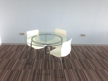 Circular glass meeting table with chrome frame.