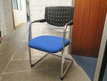 Modern chair with perforated black plastic back, upholstered seat and chrome cantilever frame