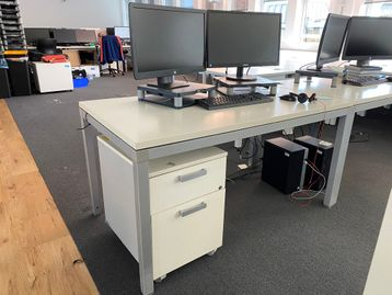 Used white rectangular free-standing desks in fair condition.