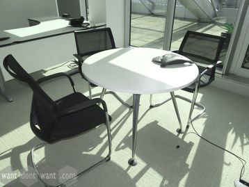 Used circular white meeting table with splayed chrome legs