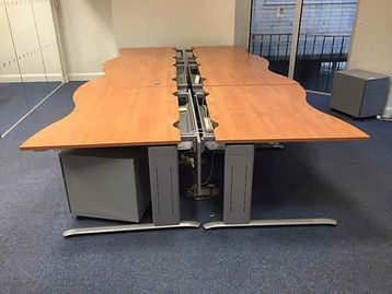 Freestanding 1400mm sliding-top double wave-shaped desks with cherry tops and silver grey frames.