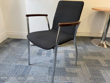 Meeting chairs upholstered in black fabric with dark wood arms and chrome legs.