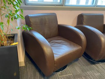 Used retro style brown faux leather armchairs
