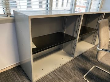 Used grey metal open-front storage units with black adjustable shelves.