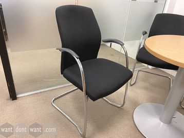 Meeting chairs upholstered in black fabric with chrome cantilever frame