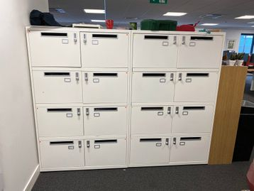 Used white 8-section locker units with letter box slots and combination locks