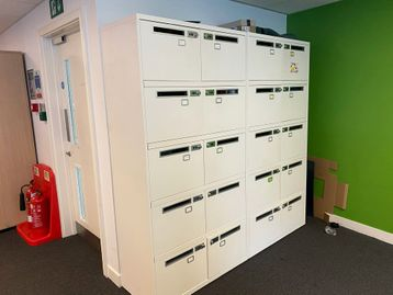 Used white 10-section locker units with letter box slots and combination locks.