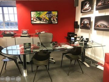 A stunning Used L-shaped executive glass desk with informal meeting end.